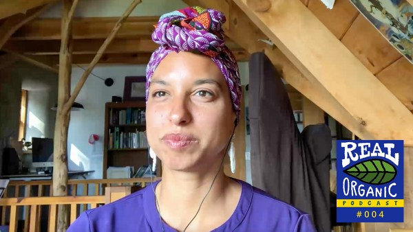 A screenshot image of Leah Penniman wearing a colorful pink and purple hair wrap and purple shirt.