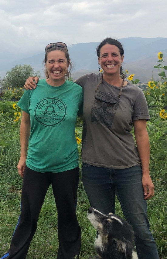 Linley Dixon and Jessica McAleese  smile and have their arms around one another with a farm in the background.