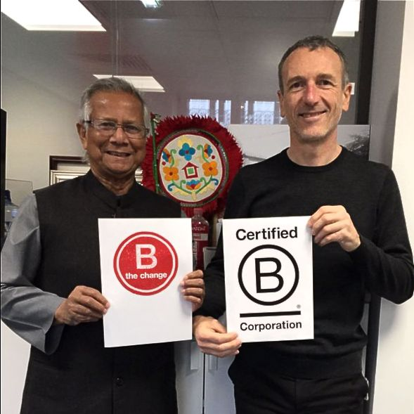Emmanuel Faber posing with a colleague. Both hold B Corp signs and smile for the camera.