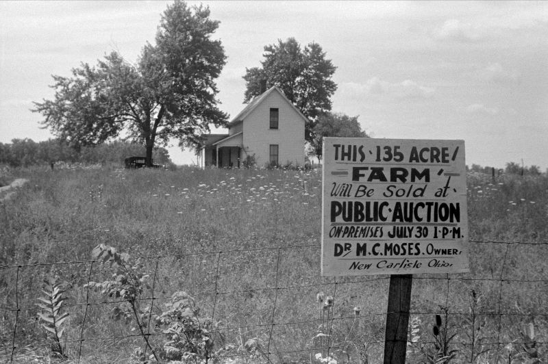 """An archived black and white photo of a white farmhouse in a field. A sign reading """"This 135 Acre Farm will be sold at public auction. On premises July 30 1PM. Dr. M.C. Moses. Owner. New Carlisle, Ohio."""