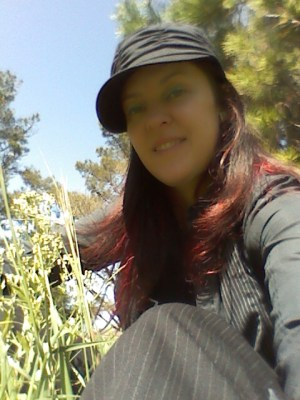 smiling woman with long red hair, wearing a black cap, black pinstripe pants and a black long sleeve button down shirt, sitting in tall grass with pine trees behind her.
