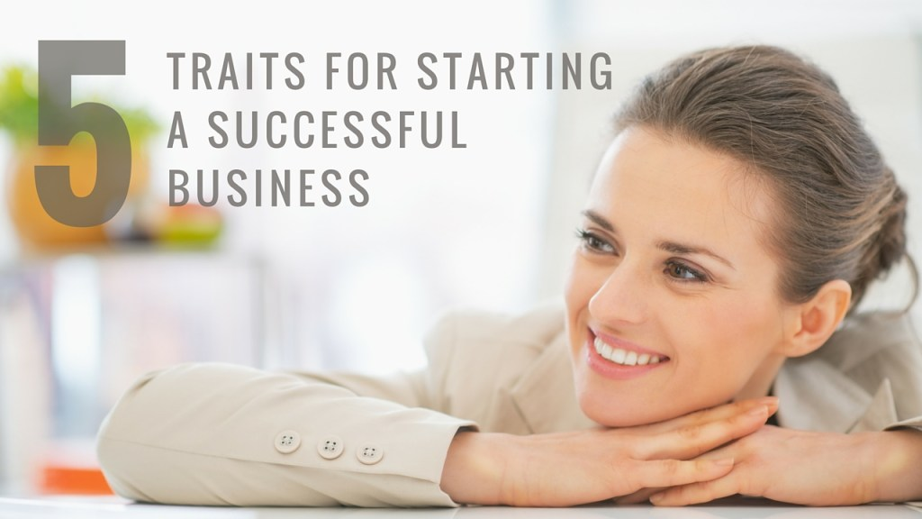 business woman with her hands folded on the table and her chin on her hands looking to the left and smiling