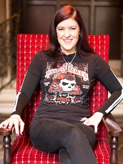 smiling woman sitting on a red velvet chair