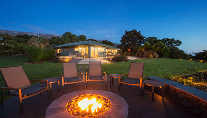chairs surrounding a fire pit outside the house