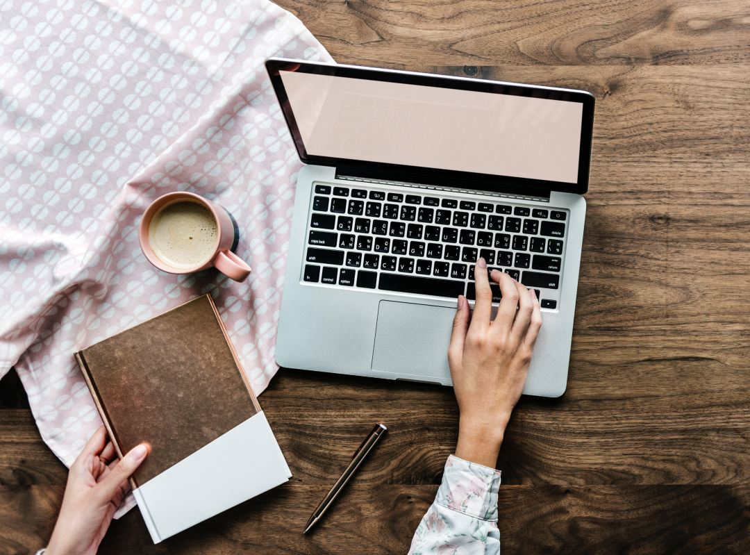 Woman creating website design beside a book and cup of coffee.