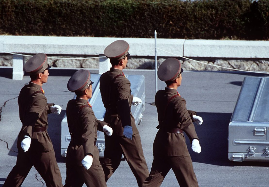 North Korean soldiers in brown uniforms march in formation on an army base complex.
