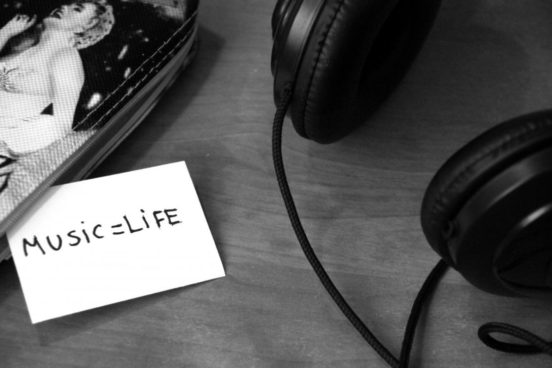 "A pair of headphones laid on a table, next to a handwritten note that reads ""Music equals life""."