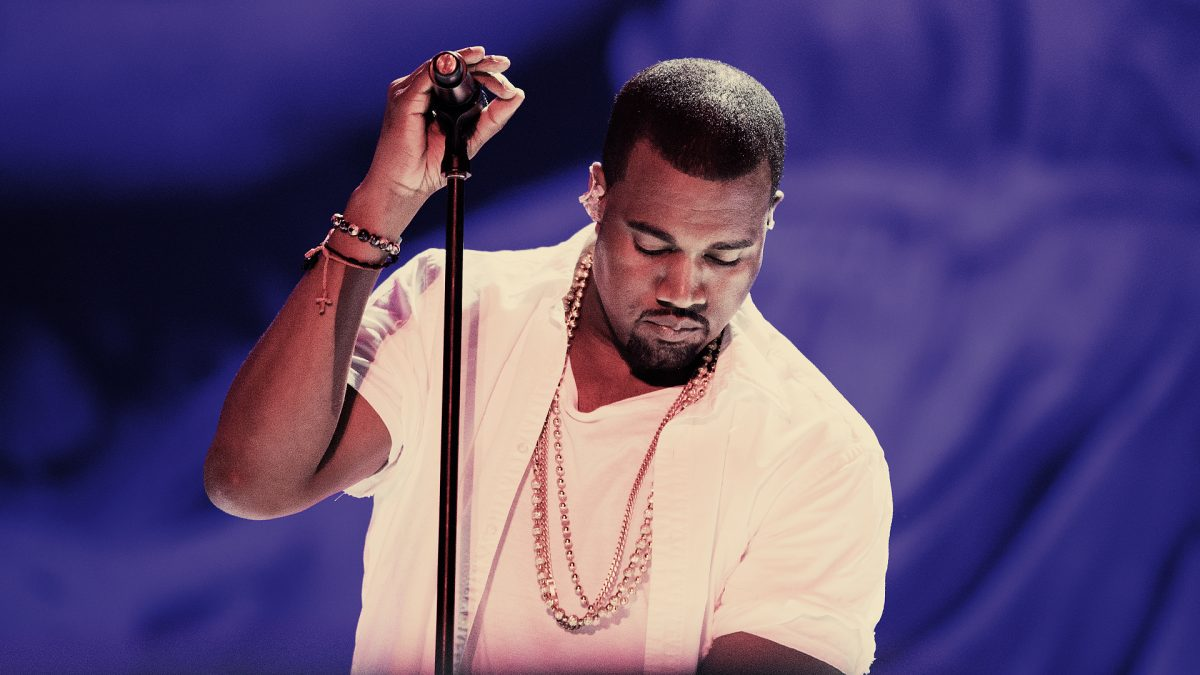 Kanye west wearing a white shirt and gold chains, holding onto a microphone stand with his right hand.