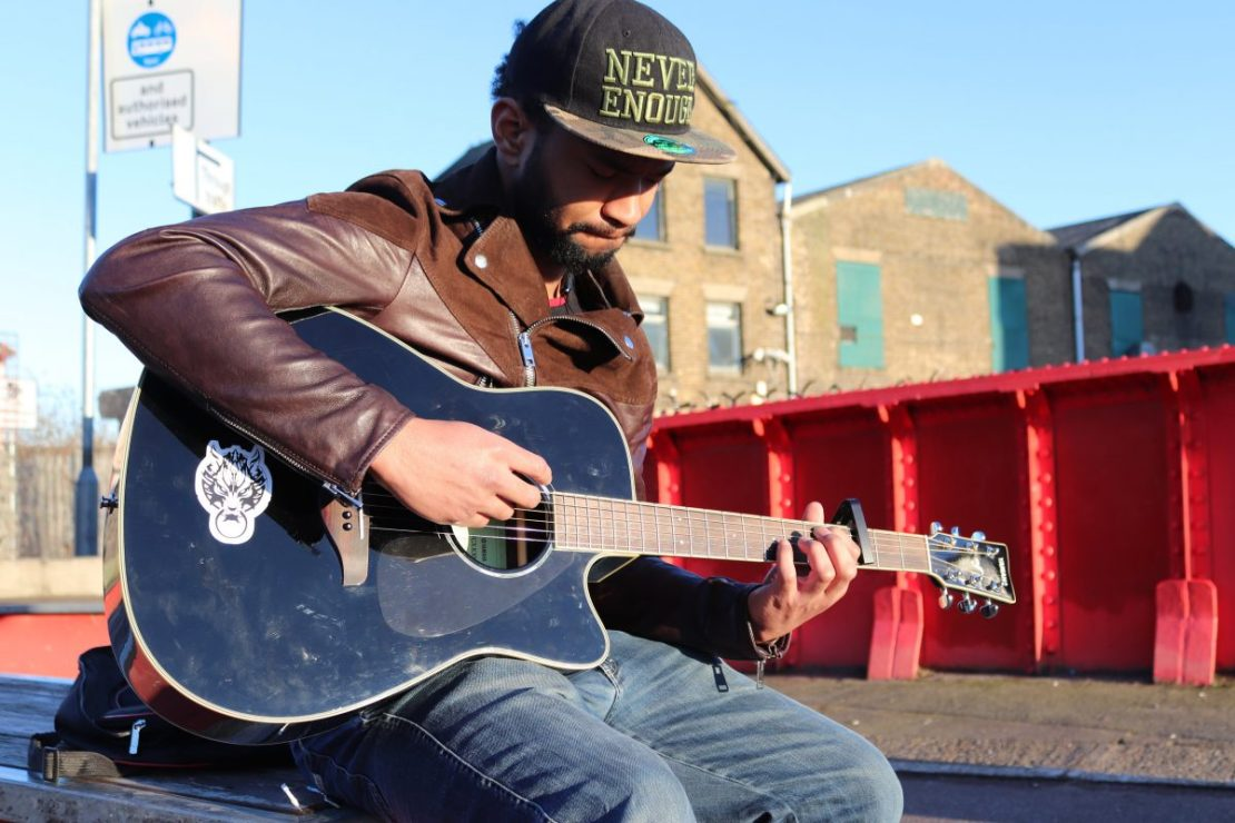 A person with a dark beard, black cap and brown leather jacket plays a black acoustic guitar.