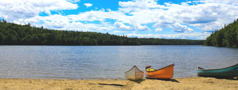 canoes on edge of lake with bright blue sky and clouds