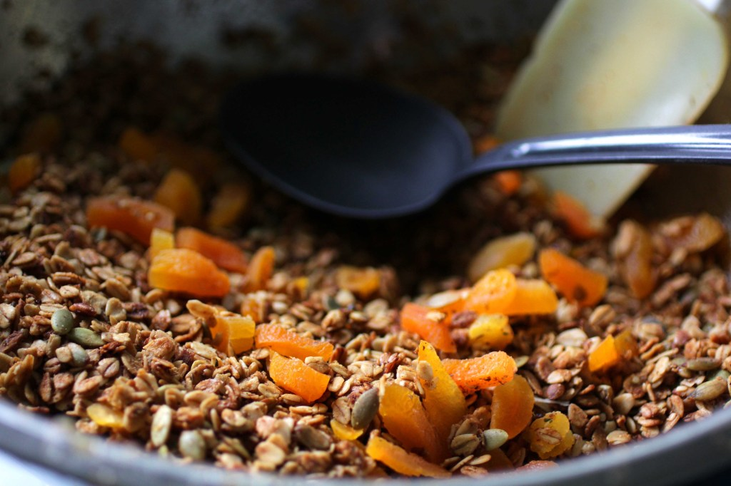 close up of homemade granola with ginger and apricot being mixed