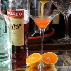 Satsuma orange and luxardo bitter cocktail being poured into a martini glass next to a cut open satsuma