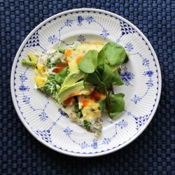 overhead shot of scrambled eggs garnished with watercress and avocado served on a white plate with blue accents, all on a blue background