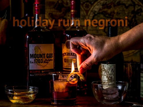 holiday rum negroni with fire and boozy orange peel