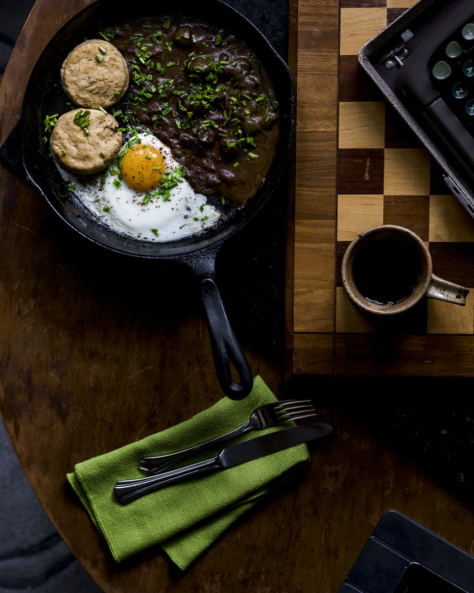 Overhead shot of a green napkin and silver place setting on a wood table with a cast-iron skillet with one over easy egg, two biscuits, and the Guinness and Mushroom Gravy topped with chopped chives. Next to a typewriter and a coffee in a brown pottery mug