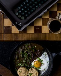 Overhead shot of a cast-iron skillet with one over easy egg, two biscuits, and the Guinness and Mushroom Gravy topped with chopped chives. Next to a typewriter and a coffee in a brown pottery mug