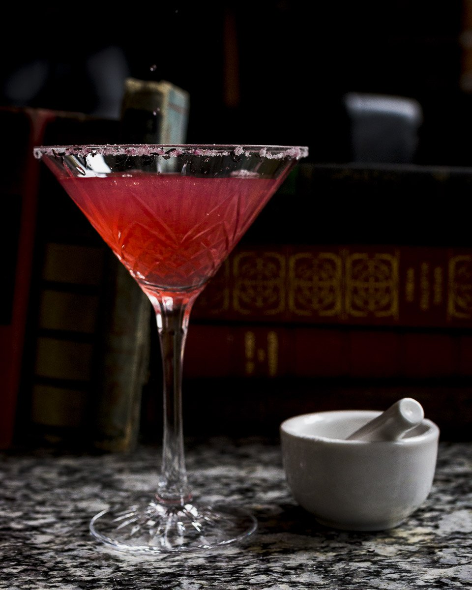 pouring a hibiscus infused vodka sidecar with a hibiscus sugar rim