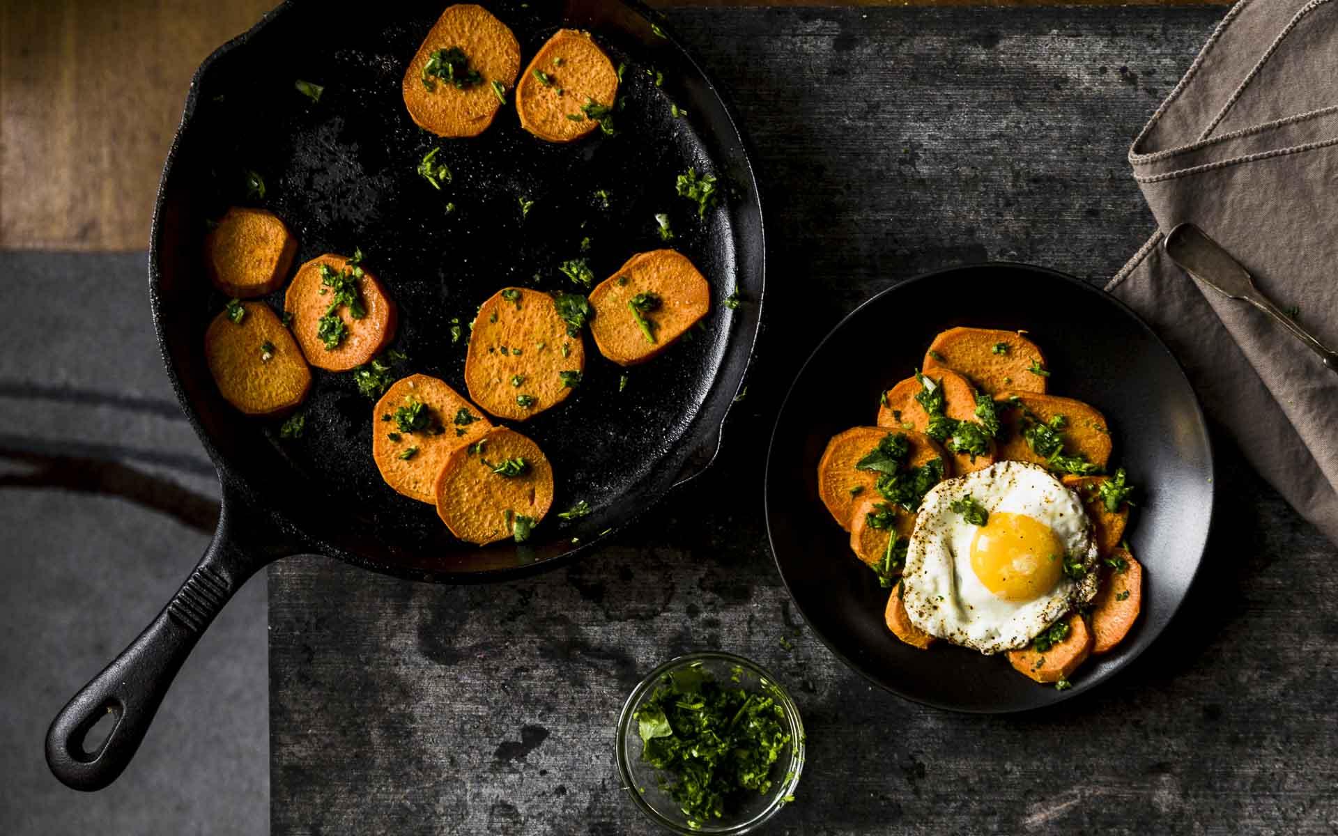 overhead shot of spicy sweet potatoes w/cilantro sauce in cast iron pan