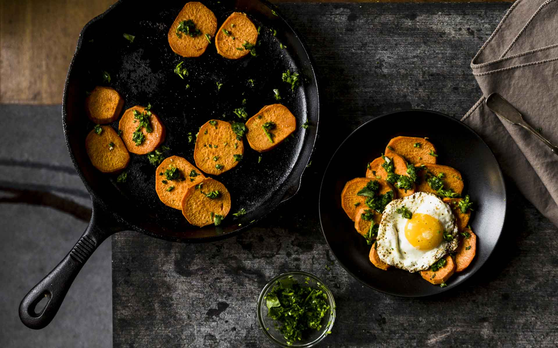 overhead shot of spicy sweet potatoes w/cilantro sauce in cast iron pan