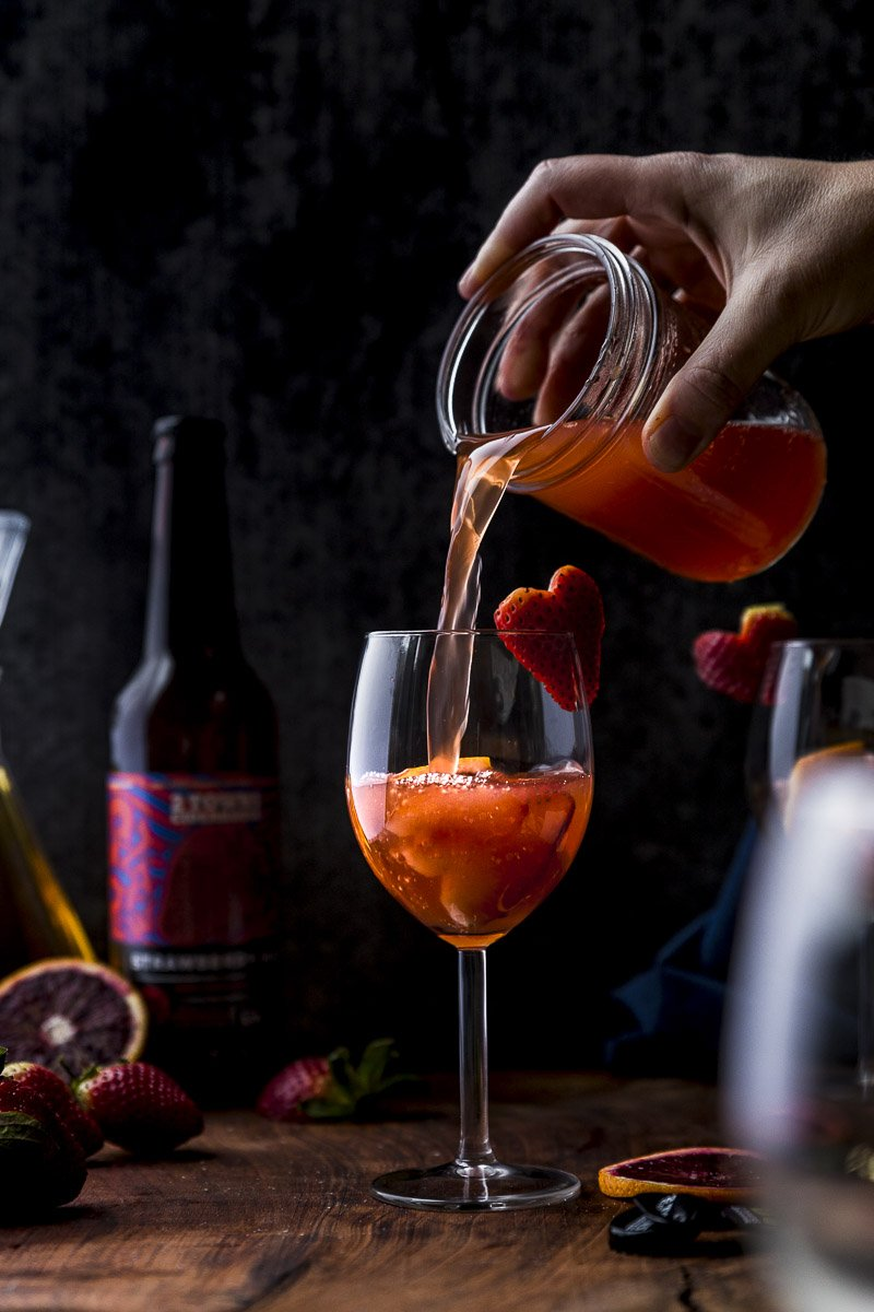 pouring a wine glass of strawberry hard cider sangria with heart shaped strawberry garnish