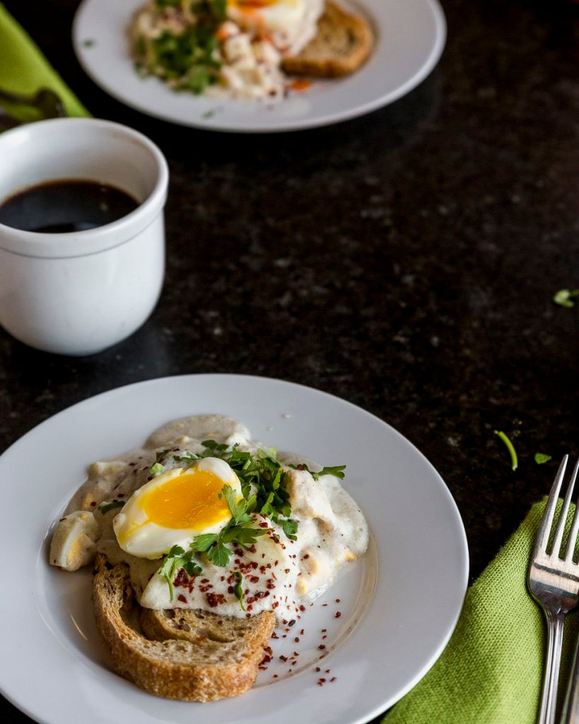 fourty five degree angle of creamed eggs on toast on a white plate with a green napkin