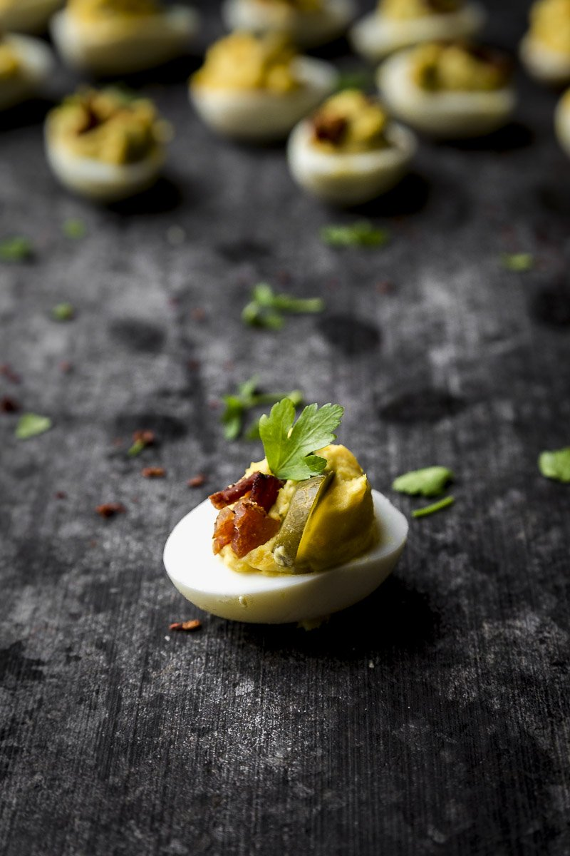 close up of a no recipe deviled egg with pickle brine and bacon