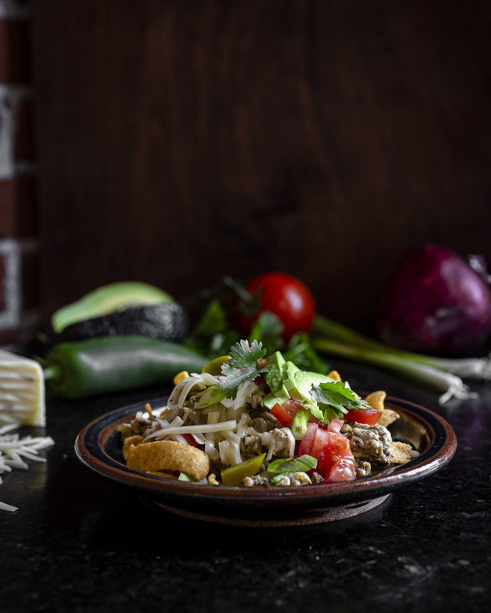 a single serving of frito pie made with ground turkey and green chiles, topped with avocado, tomato, and cheese