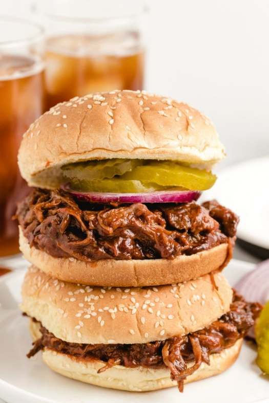 two barbecue beef sandwiches stacked on top of each other displayed on a white plate with glasses of soda in the background
