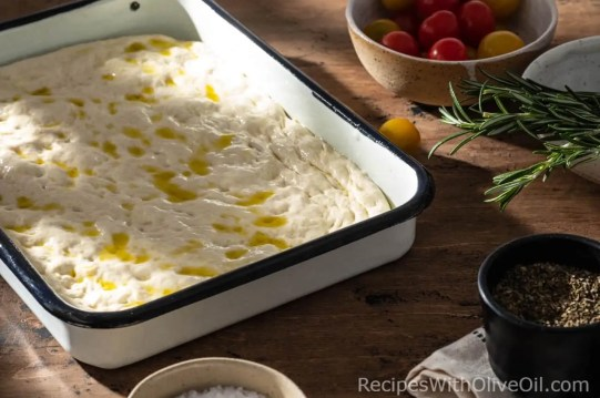 raw focaccia dough in pan with olive oil