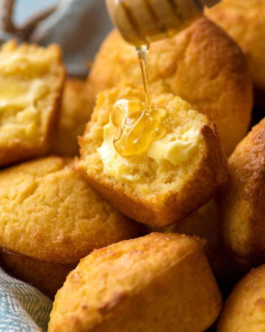 Cornbread Muffin broken in half slathered with butter and being drizzled with honey