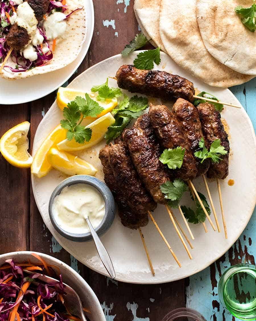 Lamb Koftas on a platter served with pita bread, minted cabbage salad and yogurt sauce