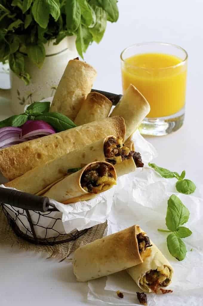 Spicy Italian Breakfast Roll Ups in a basket with glass of orange juice