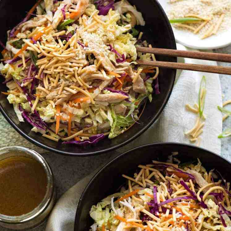 Overhead photo of 2 black bowls with Chinese Chicken Salad with Asian Dressing, ready to be eaten