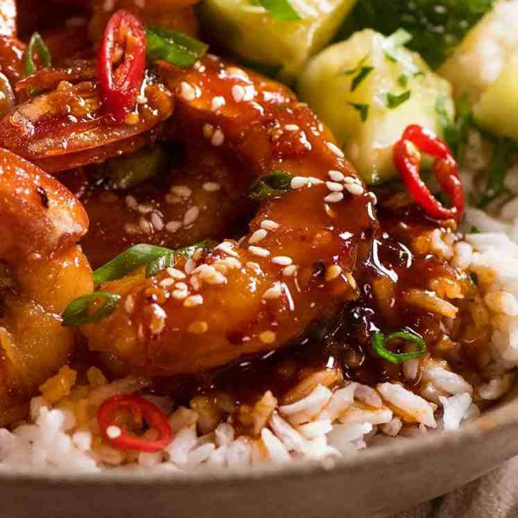 Close up of Asian Chilli Garlic Prawns served over rice with a quick Asian cucumber side salad