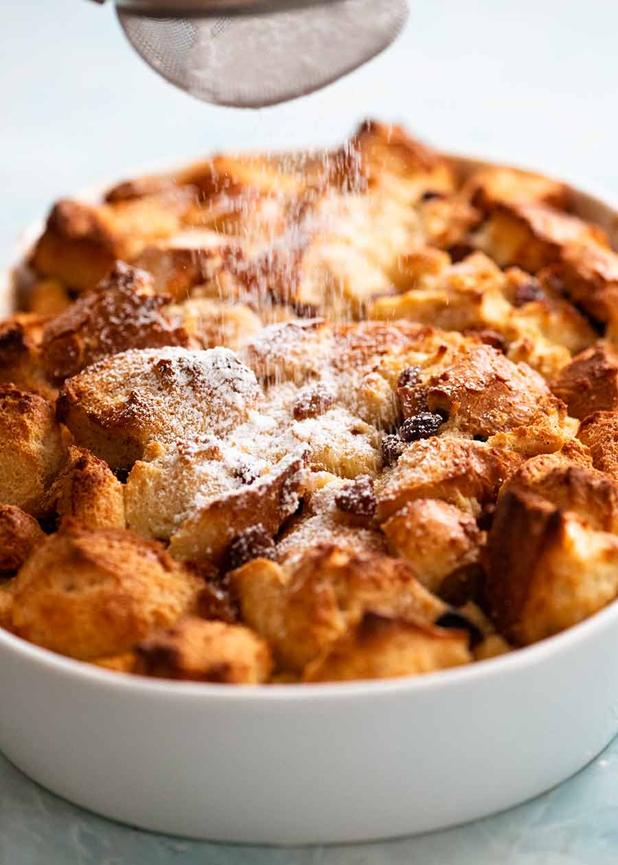 Dusting freshly cooked Bread and Butter Pudding with icing sugar