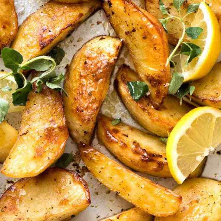 Close up of Greek Lemon Potatoes garnished with fresh oregano and lemon wedges