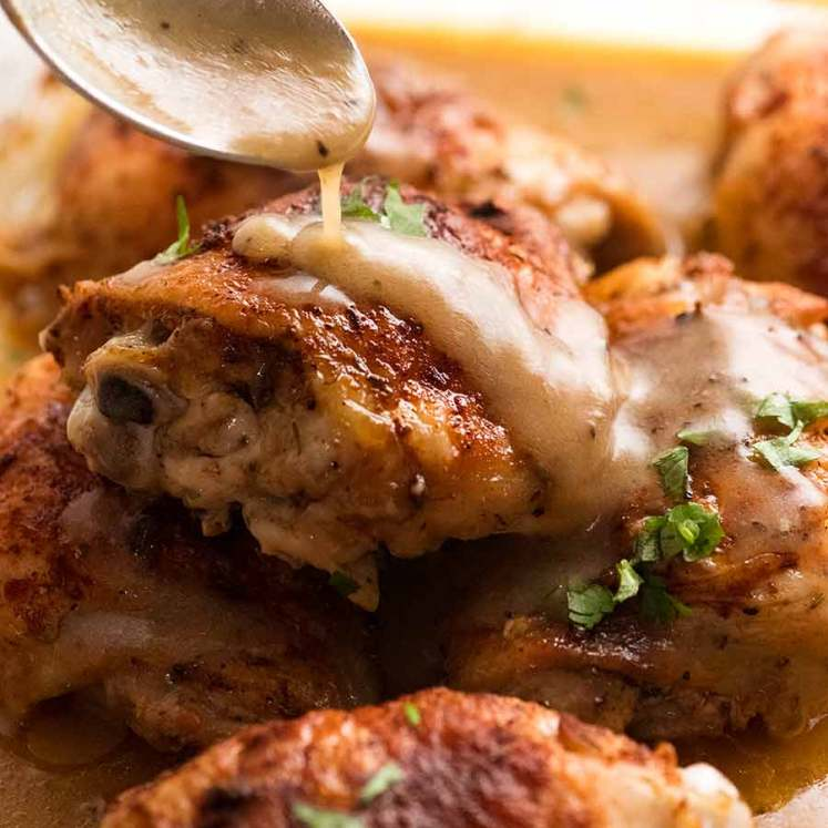 Spoon drizzling gravy over Crispy Baked Chicken in gravy
