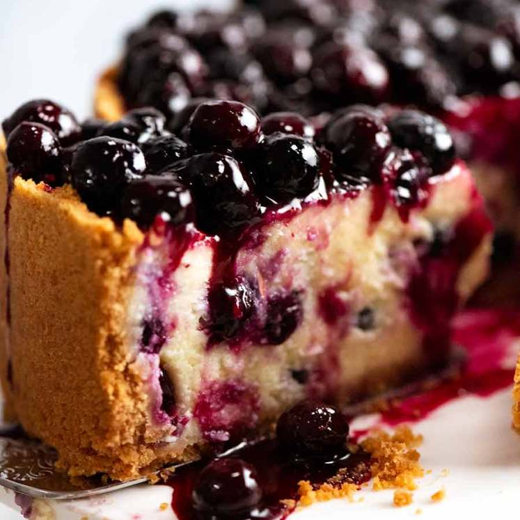 Close up of slice of Blueberry Cheesecake with drip of Blueberry Sauce