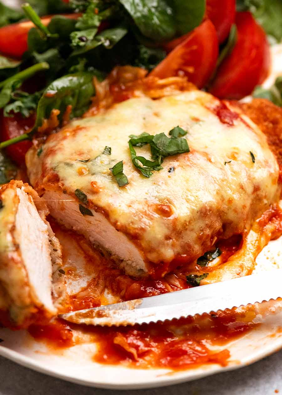 Close up of Chicken Parmigiana (Chicken Parmesan) with a garden side salad