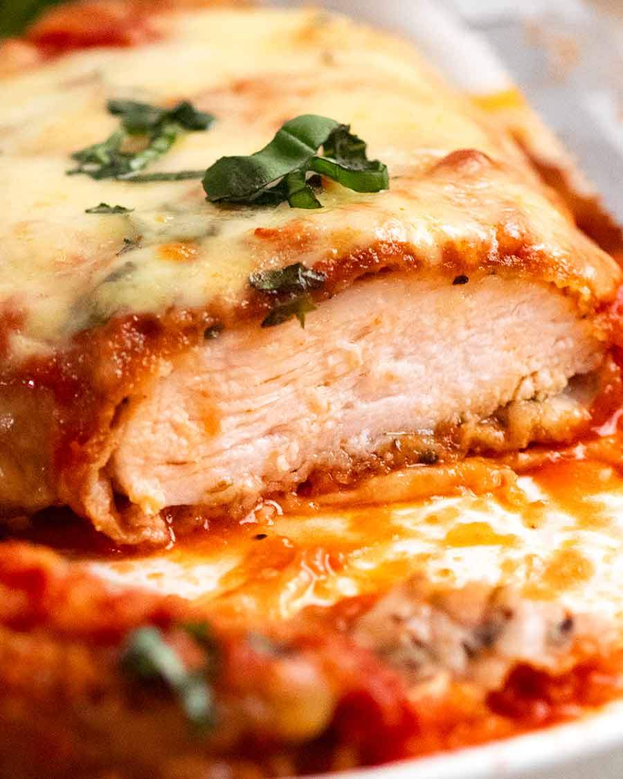 Piece of Chicken Parmigiana (Chicken Parmesan) cut open to show how juicy the chicken is inside