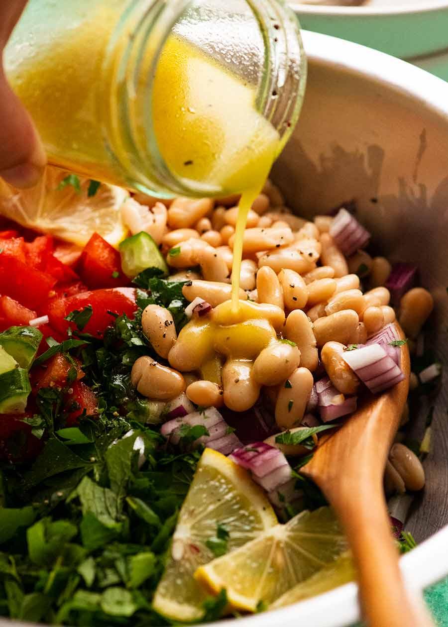 Pouring lemon dressing over White Bean Tabbouleh Salad