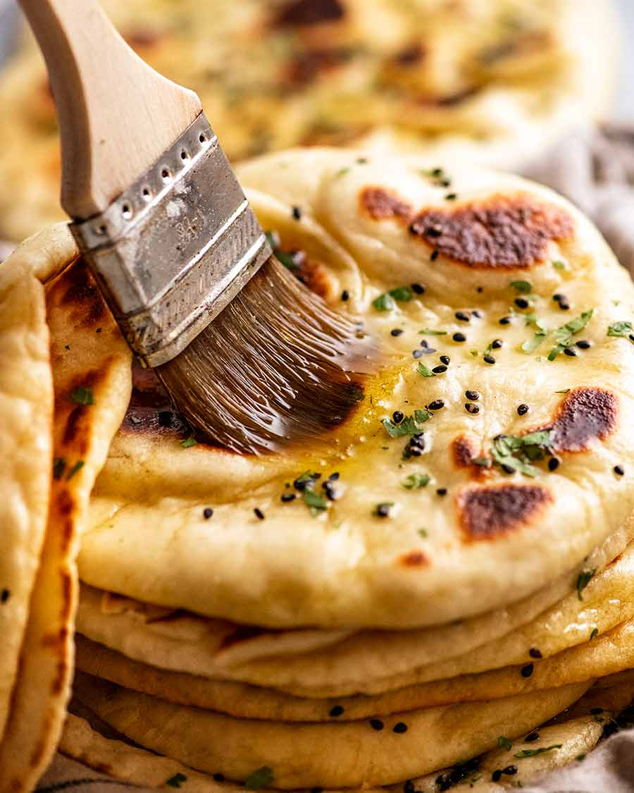 Brushing melted garlic butter on a freshly cooked naan