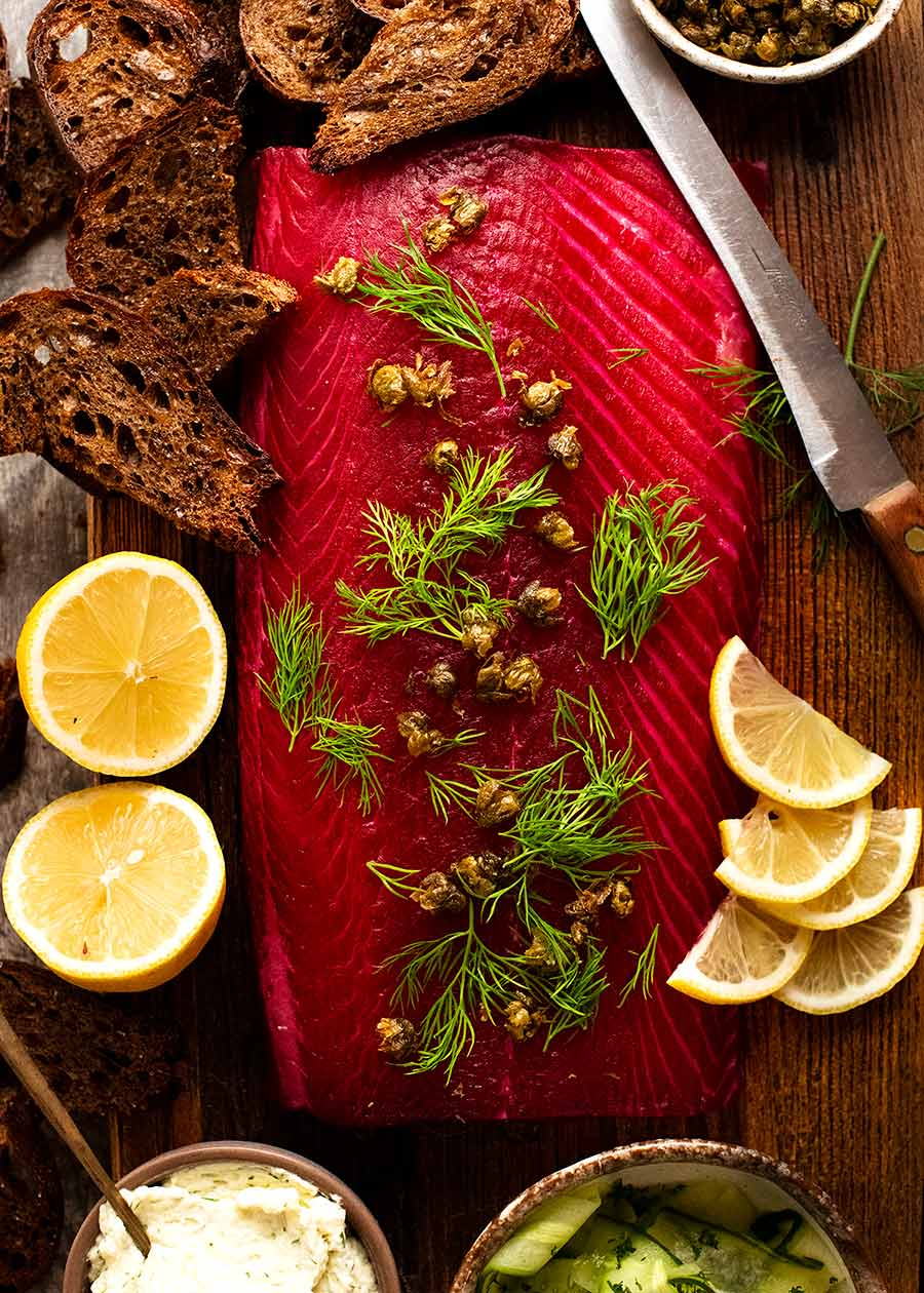 Overhead photo of Beetroot Cured Salmon (Gin or Vodka, Salmon Gravlax) on a wooden board, ready to be served