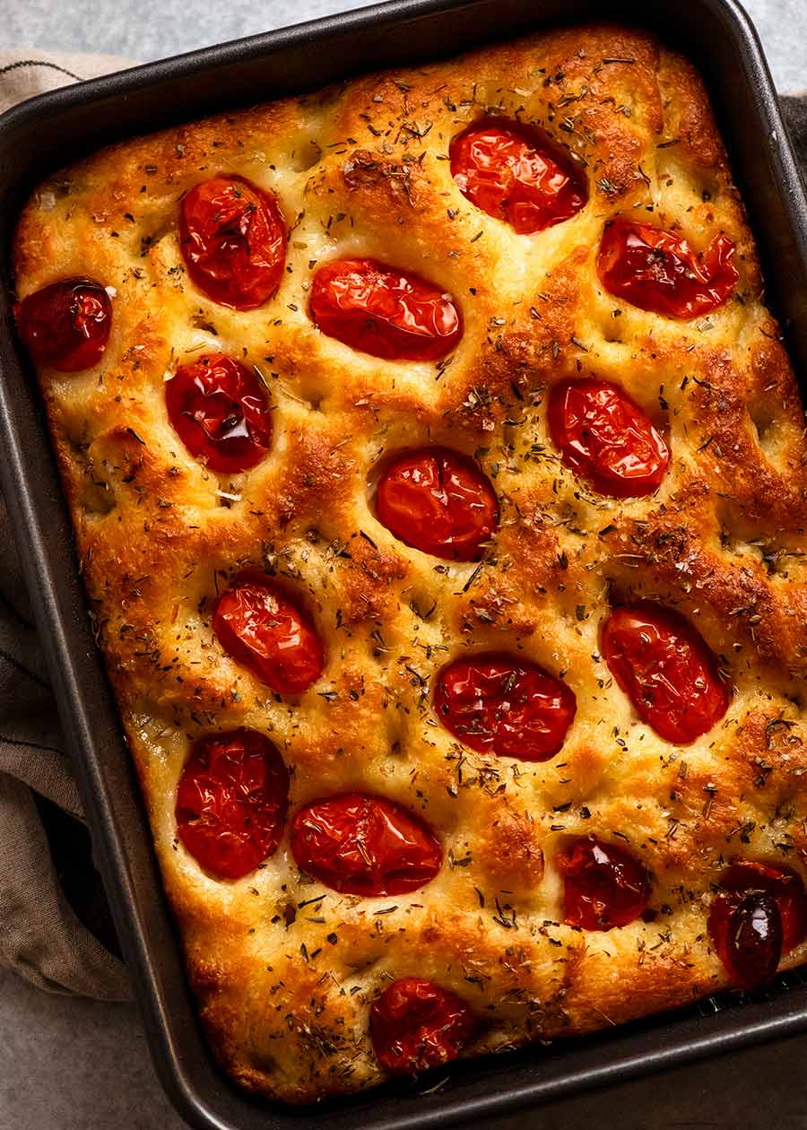Overhead photo of tomato focaccia in a pan, fresh out of the oven