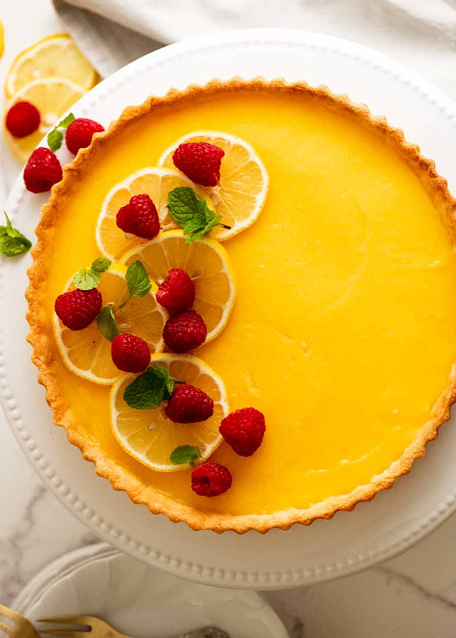 Overhead photo of French Lemon Tart decorated with raspberries and creme fraiche
