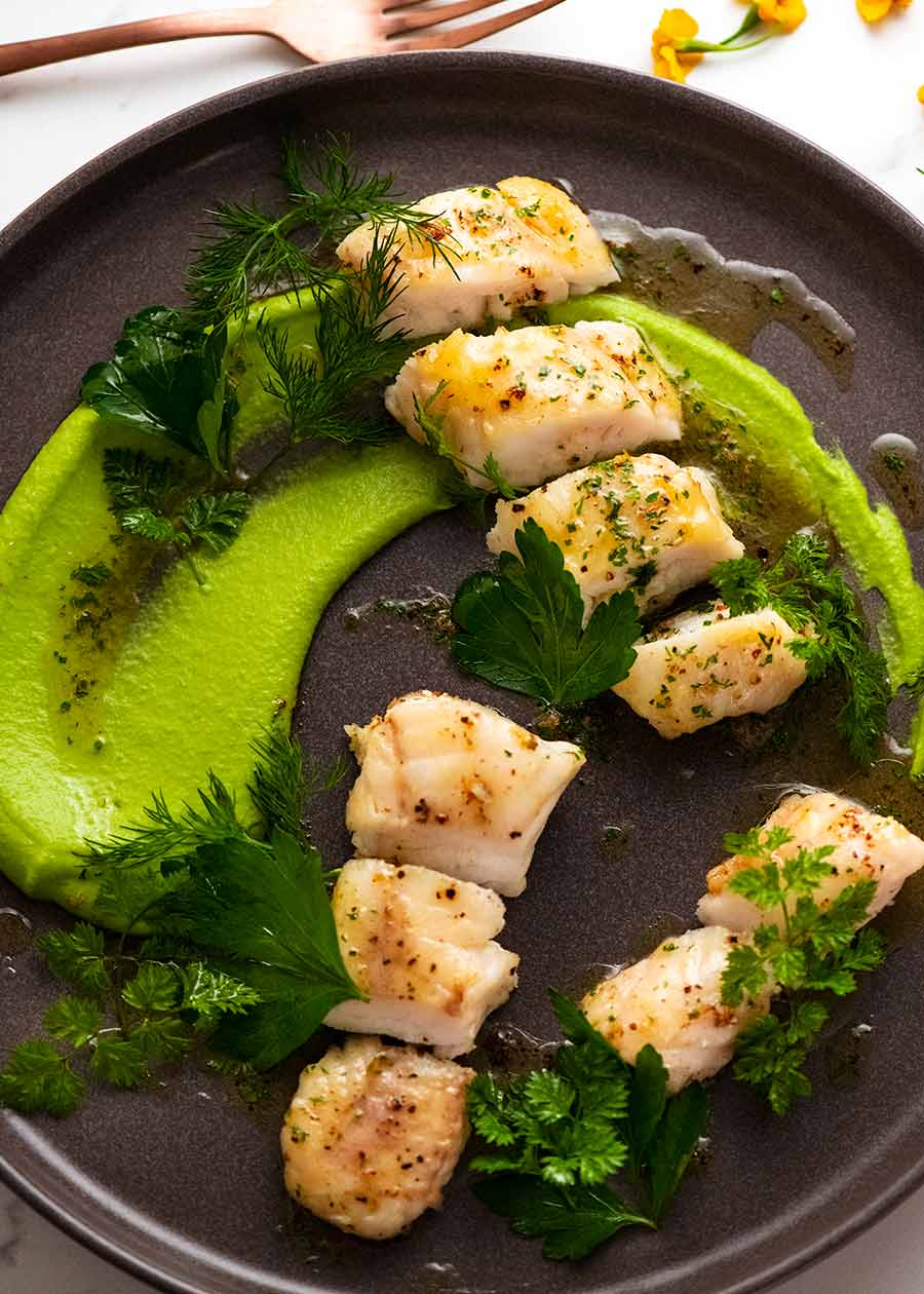 Monkfish on a plate with pea puree and Brown Butter Herb Sauce