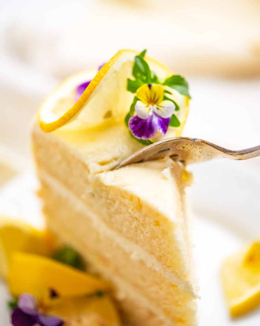 Fork cutting into piece of Lemon Cake with Fluffy Lemon Frosting