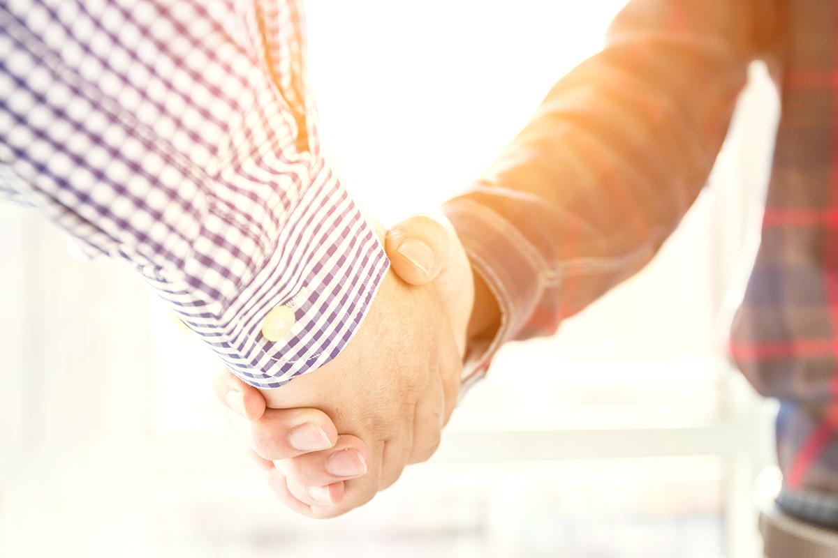 dos personas dándose la mano tras un despido. foto de reclamador.es