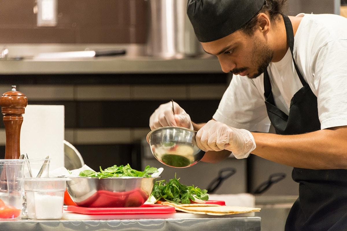 cocinero trabajando en un chiringuito en verano. foto de reclamador.es, compañía online de reclamaciones