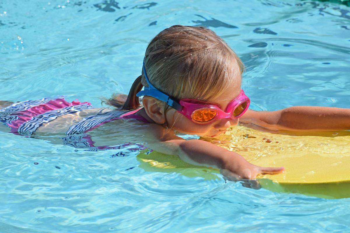 niña nadando con una tabla en una piscina en verano